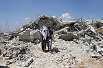Palestinians inspect their house destroyed by the Israeli army bulldozers in Pharaoh village near the West Bank city of Tulkarem, on June 9, 2014. The Israeli army bulldozers demolished the house of a Palestinian family under the pretext of building near the Israeli separation wall. Photo by Nedal Eshtayah