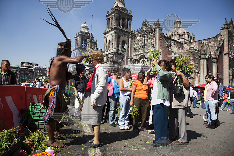 A woman receives a traditional, indigenous blessing during Christmas in front of the Metropolitan Cathedral (Catedral Metropolitana de la Asuncion de Maria).