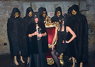 Dressed in black posing on a red and gold throne at the Veuve Clicquot Yelloween party.