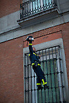 Madrid, Spain, 23/02/13. A firefighter shouts slogans standing on a window during 23F Citizen Tide, manifestation of all social movements and citizens together to protest against the financial coup and austerity measures and cuts made by the government, hundred thousand people took the streets..