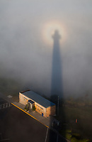Circular Rainbow around Tower caused by the refraction and dispersion of the sun's light in the fog, Astoria Column, Oregon.