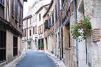 A curving street in the old town with old stone and wooden beam houses. Bergerac Dordogne France