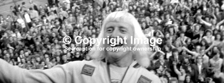 Pop idol, disc jockey, television presenter, Jimmy Savile, UK, performing at Pop Concert, Nutt's Corner, near Belfast, N Ireland, 23rd September 1973. 197309230589a<br /> <br /> Copyright Image from Victor Patterson, 54 Dorchester Park, Belfast, UK, BT9 6RJ<br /> <br /> t1: +44 28 9066 1296 (from Rep of Ireland 048 9066 1296)<br /> t2: +44 28 9002 2446 (from Rep of Ireland 048 9002 2446)<br /> m: +44 7802 353836<br /> <br /> e1: victorpatterson@me.com<br /> e2: victorpatterson@gmail.com<br /> <br /> The use of my copyright images is subject to my Terms &amp; Conditions.<br /> <br /> It is IMPORTANT that you familiarise yourself with them. They are available on my website at www.victorpatterson.com.<br /> <br /> None of my copyright images may be used on a website or on television unless they are visibly watermarked, i.e. &copy; Victor Patterson within the body of the visible image. The metadata of images used on the Internet must not be removed.<br /> <br /> Copyright acknowledgment of my images is a condition of use.<br /> <br /> Failure to observe the above conditions will incur a penalty of at least 100% of the agreed fee. <br /> <br /> Web use (maximum size - 400 kb) is extra at currently recommended NUJ rates.