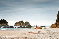 A woman on remote, wild West Coast beach - South Westland, West Coast, New Zealand