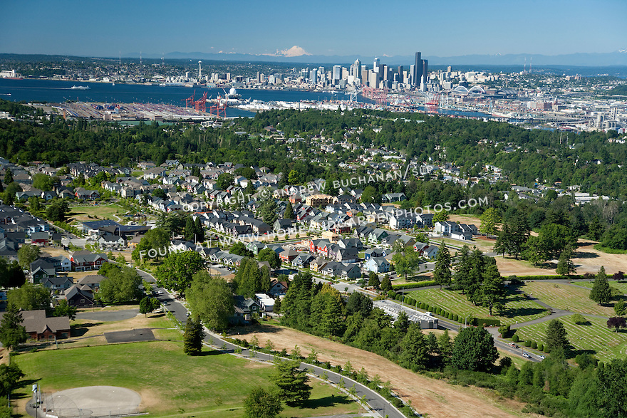 High Point, West Seattle, WA; An aerial view of High Point, a mixed housing development in West Seattle, with the Seattle skyline, Mt. Rainier, and Puget Sound in the background.