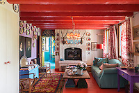 This cosy and colourful living room has a red-painted floor and ceiling with a tantalising glimpse through an open door to the turquoise-painted kitchen