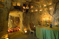 Tealights and candles nestled in roughly-hewn niches illuminate the dining room and ajoining alcove bedroom of this folly
