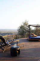 Sun loungers and a daybed give a stunning view overlooking the surrounding countryside from a terrace of the Singita Pamushana Lodge, Malilongwe Trust, Zimbabwe