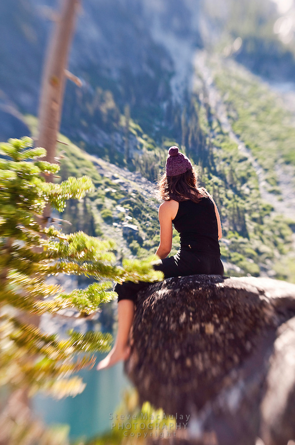 Campsite scene of young woman sitting on a rock in the sun, Colchuck Lake, Alpine Lakes Wilderness, WA.