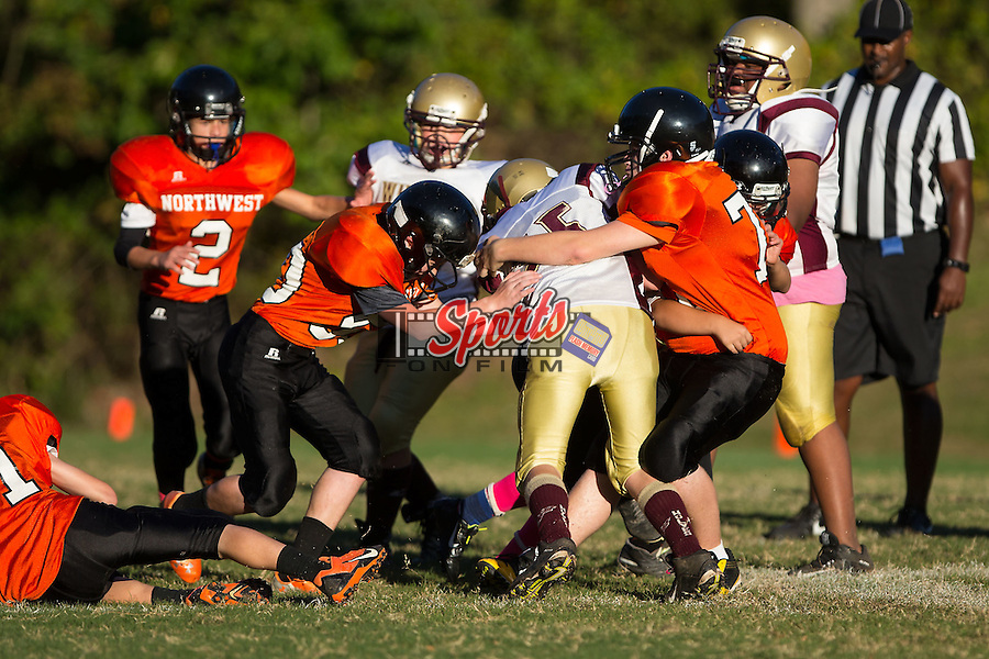 Winkler Wolves running back #35 is tackled by Nathaniel Smith (51) and Ethan Ellison (77) of the Northwest Cabarrus Titans in 7th grade football action at Trojan Stadium October 7, 2014, in Concord, North Carolina.  The Titans defeated the Wolves 58-30.  (Brian Westerholt/Sports On Film)