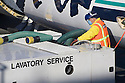 A ground crew worker providing lavatory service for an Boeing airplane by Alaska Airlines, San Francisco, California, USA