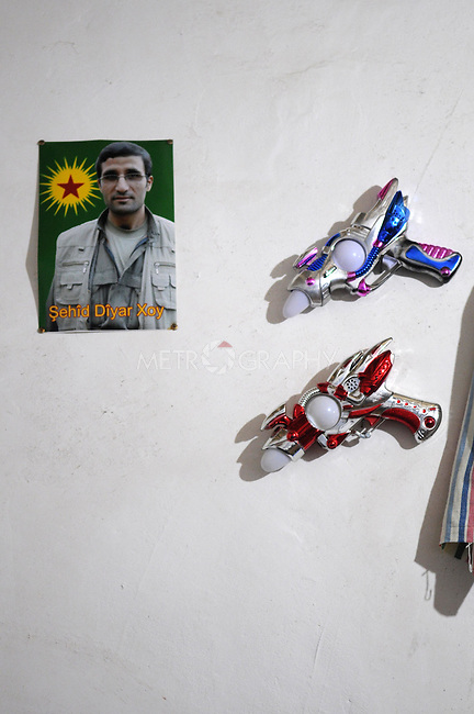 QANDIL, IRAQ:  A poster of a dead PKK guerrilla is posted next to a set of toy gun on the wall of a house in the Qandil mountains...The Kurdistan Workers' Party (PKK) is a pro-Kurdish party in Turkey deemed a terrorist group by the USA and the EU.  They are based in the Qandil mountains that make up the border between Iraq and Turkey...Photo by Kamaran/Najm