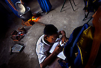 "A student writes in his notebook as other students cook rice in the background. As part of the ""life skills"" training, teams of students are formed, so that each child gets a turn at preparing and cooking the food for the school. Since the early 1990s, twin sisters Sri Rosyati (known as Rossy) and Sri Irianingsih (known as Rian) have used their family inheritance to set up and run 64 schools in different parts of Indonesia, providing primary education combined with practical skills to some of the country's most deprived children."