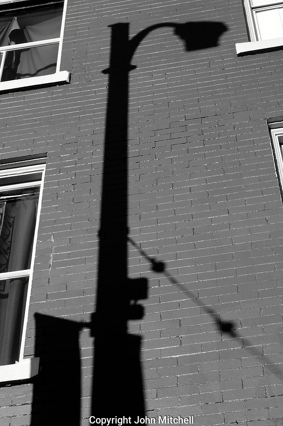 Lamp post shadow cast on the brick wall of a building in Vancouver, BC, Canada