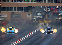 Jul. 18, 2014; Morrison, CO, USA; NHRA funny car driver Alexis DeJoria (right) races alongside Bob Tasca III during qualifying for the Mile High Nationals at Bandimere Speedway. Mandatory Credit: Mark J. Rebilas-