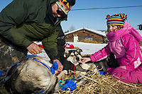 Paul Johnson boots his dogs as Ella Bird Mercer pets one Saturday morning at the Shageluk checkpoint during Iditarod 2011