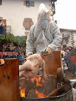 ZUBIETA, NAVARRE- JANUARY 31: A hooded man roasts a chicken during the celebration of an ancient traditional carnival in Zubieta on January 31, 2006. Photo by Ander Gillenea