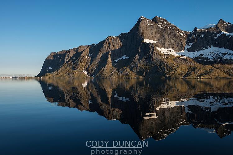 Reflection of Veinestind mountain peak with Reine in distance, Reinefjord, Moskenesøy, Lofoten Islands, Norway