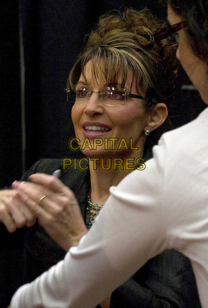 SARAH PALIN .Former Alaskan Governor and Vice Presidential candidate Sarah Palin makes a stop to promote her book 'Going Rogue: An American Life'..Thousands lined up outside the Sam's Club for a chance to meet Sarah Palin and the opportunity to have their book signed in Washington, Pennsylvania, USA, 21st November 2009..portrait headshot glasses black shirt  hair up politics american america  hand                  .CAP/ADM/JD.©Josh Drespling/Admedia/Capital Pictures