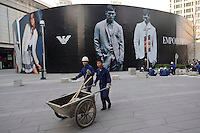 Chinese workers pave tiles in front of a huge billboard of Emporio Armani at Shin Kong Place, which is one of the most luxurious shopping centers in Beijing, having successfully attracted 938 international class brands, they also boast the largest Gucci flagship store in Asia..