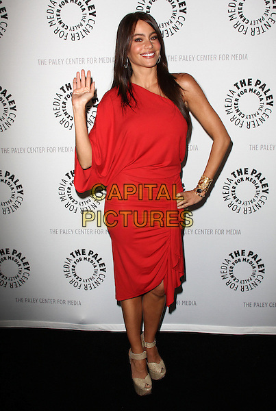 "SOFIA VERGARA.27th Annual PaleyFest Presents ""Modern Family"" held At The Saban Theatre, Beverly Glen circle, USA, .26th February 2010..full length sleeve hand on hip red one shoulder dress gold cuff bracelet shoes sandals cream beige peep toe snakeskin snake croc animal heels waving .CAP/ADM/KB.©Kevan Brooks/AdMedia/Capital Pictures."