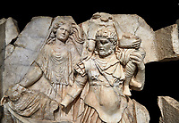 Close up of a Roman Sebasteion relief  sculpture of Aineas' flight from Troy, Aphrodisias Museum, Aphrodisias, Turkey.   Against a black background.<br /> <br /> Aineas in armour carries his aged farther Anchises on his shoulders and leads his young son Lulus by his hand. They are fleeing from the sack of Troy. The figure floating behind is Aphrodite, Aineas' mother: she is helping their escape. Old Anchises carries a round box that held images of Troy's ancestral gods.