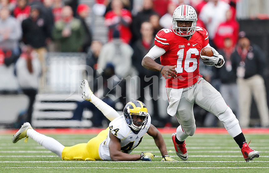 Ohio State Buckeyes quarterback J.T. Barrett (16) keeps the ball and evades a tackle from Michigan Wolverines defensive back Delano Hill (44) in the second quarter the college football game between the Ohio State Buckeyes and the Michigan Wolverines at Ohio Stadium in Columbus, Saturday morning, November 29, 2014. As of half time the Ohio State Buckeyes and Michigan Wolverines were tied 14 - 14. (The Columbus Dispatch / Eamon Queeney)