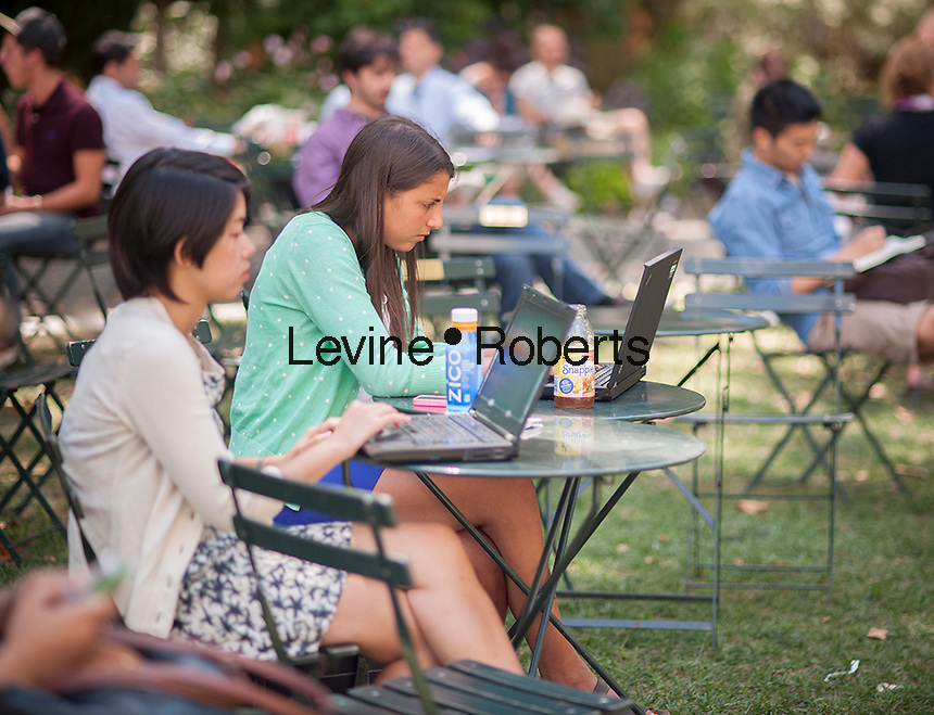 Women working together in Bryant Park in New York use their laptop computers on Thursday, August 15, 2013.  (© Richard B. Levine)