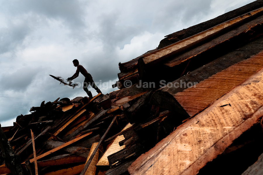 A Colombian worker, carrying wood cutoffs, walks on a pile of boards at a sawmill in Tumaco, Colombia, 17 June 2010. Tens of sawmills located on the banks of the Pacific jungle rivers generate almost half of the Colombia's wood production. The wood species processed here (sajo, machare, roble, guabo, cargadero y pacora) are mostly used in the construction industry and the paper production. Although the Pacific lush rainforest in Colombia is one of the most biodiverse area of the world, the region suffers an extensive deforestation due to the uncontrolled logging in the last years.