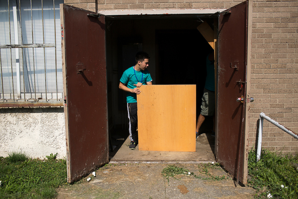 "Donald Franks moves old furniture to a dumpster during ""Circle the City with Service,"" the Kiwanis Circle K International's 2015 Large Scale Service Project, on Wednesday, June 24, 2015, at the Friendship Westside Center for Excellence in Indianapolis. (Photo by James Brosher)"