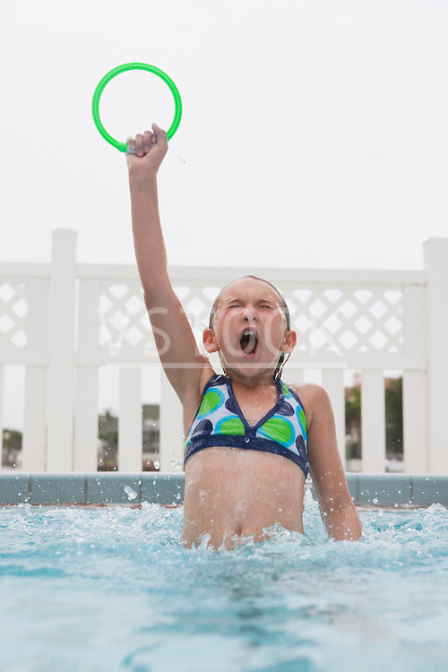 USA, Florida, St. Pete Beach, Girl (8-9) jumping out of water with toy ring