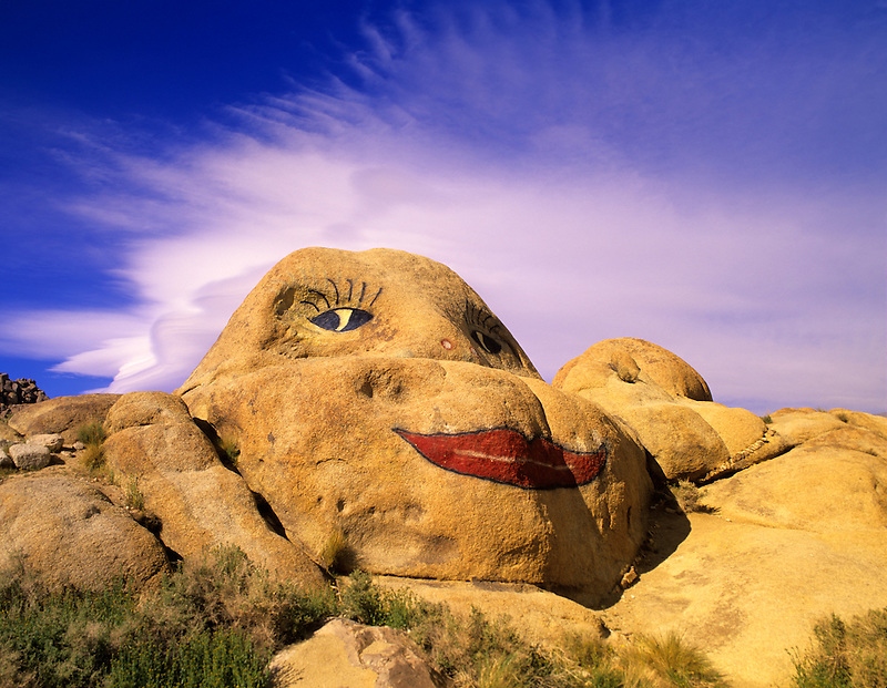 Face painted on rock w/clouds as hair. Alabama Hills, California