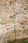 Copper lightning conductor running down a church wall into the ground