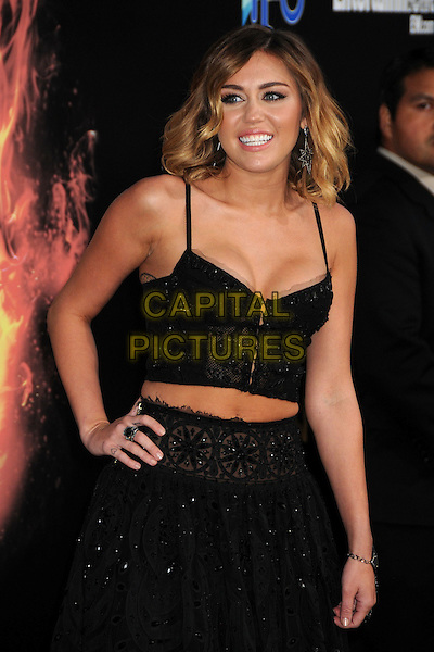 "Miley Cyrus.""The Hunger Games"" Los Angeles Premiere held at Nokia Theatre LA Live, Los Angeles, California, USA..March 12th, 2012.half length black lace sheer skirt top belly stomach midriff cleavage hand on hip.CAP/ADM/BP.©Byron Purvis/AdMedia/Capital Pictures."