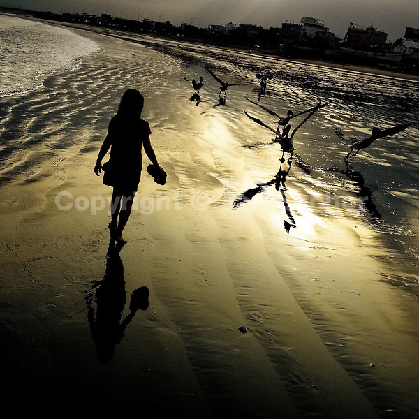 A girl walks on the low-tide beach at the sunrise in Manta, Ecuador, 20 November 2014.