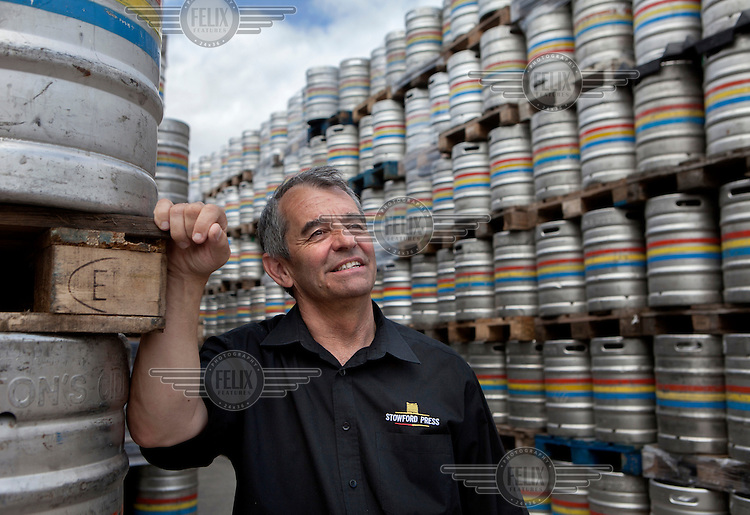 Master Cider Maker Jonathan Blair standing next to barrels of cider stacked at Westons Cider near the town of ledbury.