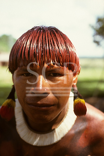 Posto Leonardo, Xingu, Brazil. Man with hair dyed with red Urucum paste and colourful feather ear rings; Xingu tribe.