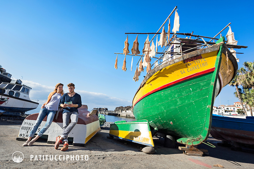 A couple traveling on Madeira Island explores the harbor village of Camara De Lobos with it's colorful fishing boats