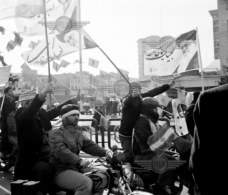 Men on motorbikes wave flags emblazoned with the image of Ayatollah Ali Hosseini Khamenei as they ride through the streets celebrating the 35th anniversary of the Iranian Revolution.