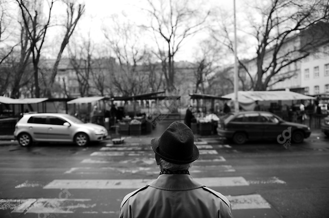 On Csengery Street a man waited to cross the road to the open air part of a market. Budapest, Hungary, March 23, 2008