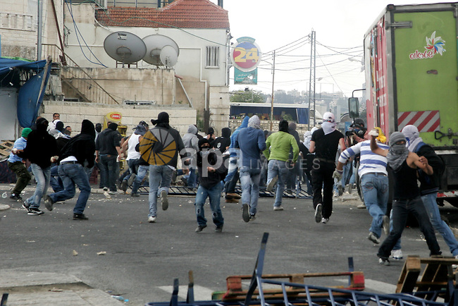 Palestinian youths throw stones during clashes following the funeral of a teenager who died after being shot as Palestinians launched events to mourn the 1948 creation of the Jewish state in Jerusalem the day before, after his funeral in the East Jerusalem neighbourhood of Ras al-Amud May 14, 2011. In the background is Islam's third holiest shrine the Dome of the Rock. Photo by Mahfouz Abu Turk