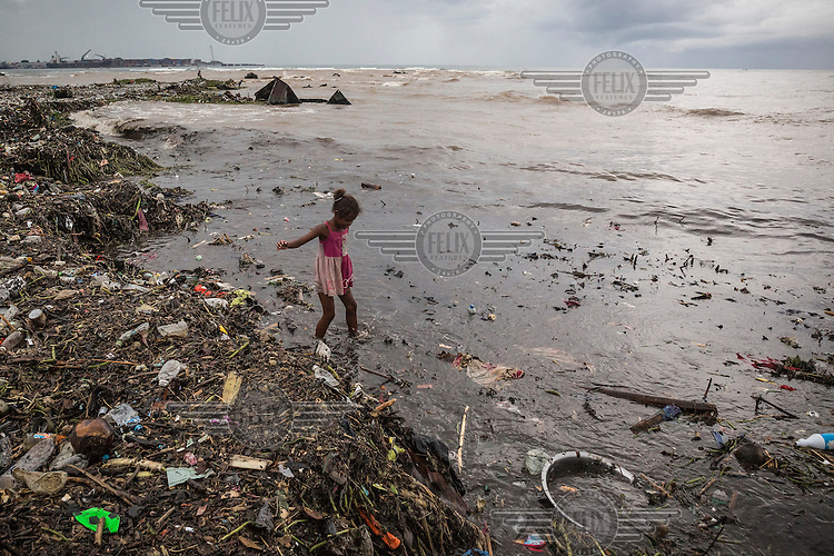 A girl walks on a beach, at Lord Howe Settlement, its shoreline thick with flood debris brought in by the tide.In February 2015, on Guadalcanal Island, tropical rains fell almost non-stop. The resulting floods caused the water level to rise for several days. It is thought that these events happened because of changes in weather patterns caused by El Nino and climate change.<br /> Lord Howe Settlement, a district of the capital Honaria, is populated by people from Ontong Java Atoll (AKA Lord Howe Atoll), a Polynesian outlier of the Solomon Islands. Its people have been moving to Lord Howe Settlement in search of a better life since the 1970s. Climate change leading to rising sea levels and consequent food insecurity now means the atoll is existentially threatened. The remaining Ontong Javanese people are considering the possibility of complete relocation to Santa Isabel Island and to Honiara. However, with Lord Howe Settlement itself suffering the consequences of extreme weather and overcrowding, community leaders believe it is not a viable long term home. Furthermore, they fear that the Ontong Javanese people's Polynesian identity will be lost as a new generation is brought up in a location with no connection to ancestral land. Their identity will be weakened as they become a minority amongst Melanesian communities that have vastly different traditions and speak different languages.