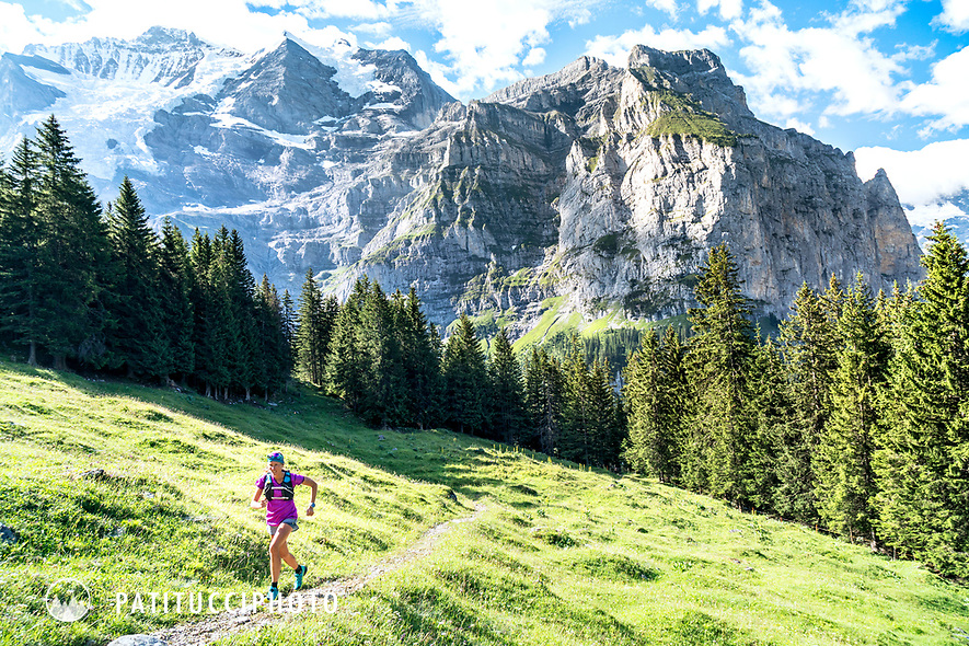 A woman trail running above Lauterbrunnen, Switzerland with the Jungfrau in the background.