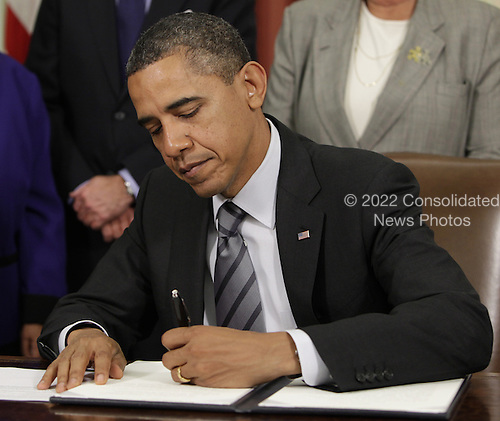 United States President Barack Obama signs an Executive Order to cut waste and promote efficient spending across the federal government in the Oval Office of the White House in Washington, DC on Wednesday, November 9, 2011. .Credit: Yuri Gripas / Pool via CNP