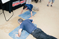 Men hold a push up contest at the New Hampshire National Guard stand at the Hillsborough Balloon Festival in Hillsborough, New Hampshire. South Carolina Senator and Republican presidential candidate Lindsey Graham walked around the festival grounds to introduce himself to New Hampshire voters.