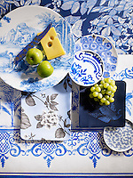 Still life of patterned plates overlapping each other. The patterns are mainly blue and floral. There are also two apples, a chunk of yellow cheese and a bunch of green grapes. Styling by Victoria Tunstall.