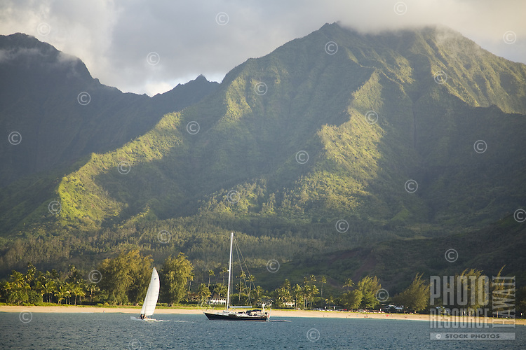 A yacht and a catamaran anchored in Hanalei Bay, with Namolokama Mountain in the background