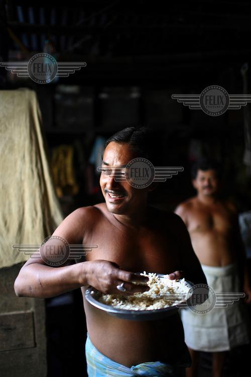 Day labourer taking lunch in a slum in Kolkata.