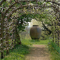 A giant urn stands at the end of this arbour
