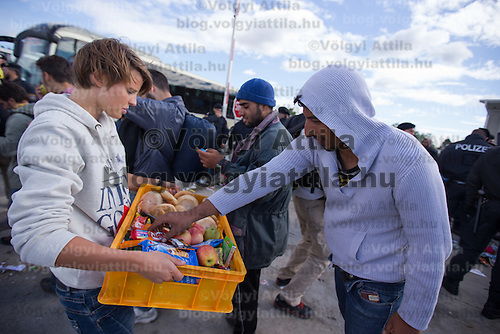 Illegal migrants traveling to Germany receive food from a volunteer at Hegyeshalom border crossing (about 180 km West of capital city Budapest), Hungary on September 06, 2015. ATTILA VOLGYI